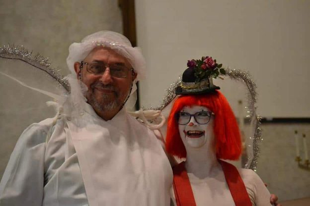 Man dressed up as an angel and woman with orange hair and clown make up