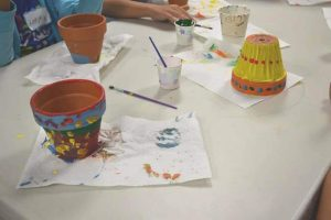 Photo of paints and brushes with flower pots on paper on the table