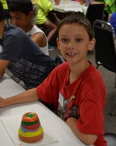 VBS camper at table with painting project