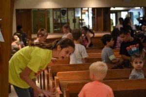 Photo of a young woman in a yellow shirt talking with a boy in a pew in the Sanctuary.