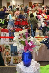 Flower in the foreground and other items and shoppers in the background