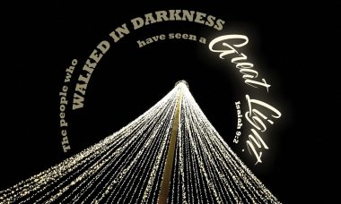 "Photo of strings of lights on a black background with the words, ""The people who walked in darkness have seen a great light."""
