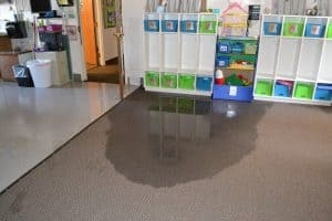 Carpet with a puddle of standing water in the Preschool wing