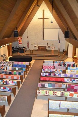 Photo of Mt Olive's Sanctuary from above with multi-colored quilts on the backs of all the pews