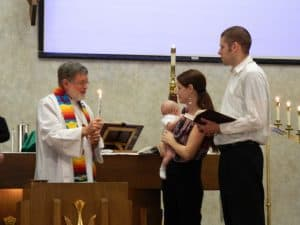 Pastor Jack holding candle and man, woman and baby beside the baptismal font