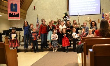 Children standing in the front of the Sanctuary to sing and the screen is visible with lyrics displayed