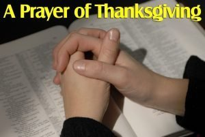 """Photo of hands clasped together on an open book as in prayer with the words """"A prayer of Thanksgiving."""""""