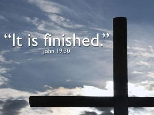"Photo of the top of a cross against the sky with clouds and the words, ""It is finished."""
