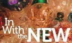 "The words, ""In with the New,"" on a background of Christmas ornaments and tinsel."