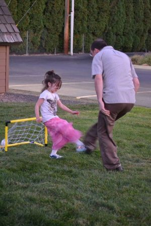 Photo of a man kicking a soccer ball with a young girl defending the net.