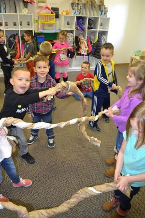 Photo of children in a classroom with ropes they have made of paper.