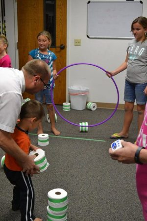 Photo of an adult helping a child with a game using hoops and rolls of toilet paper.