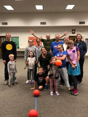 Photo of a group of people with adults in back and children in front holding balls