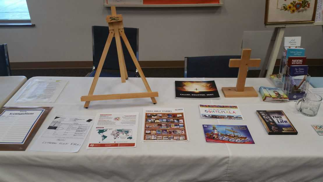 Table with several papers and flyers, a cross and an easel