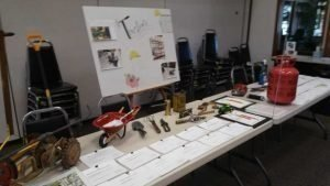 "Table with miniature wheelbarrow, tractor and various tools with a Poster behind with the title ""Trustees"""