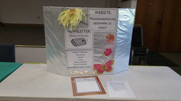 """Table with a poster board holding four posters with titles """"Website"""" """"Newsletter"""""""