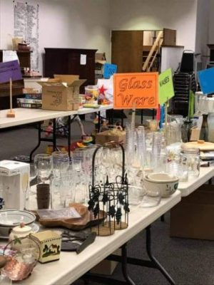 Photo of a table covered with yard sale items and other tables in the background