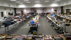 Photo of Fellowship Hall with tables arranged in long rows covered with yard sale items