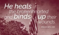 "Photo of a flag with the words, ""He heals the brokenhearted and binds up their wounds."""