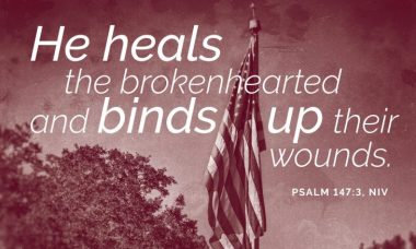 """Photo of a flag with the words, """"He heals the brokenhearted and binds up their wounds."""""""