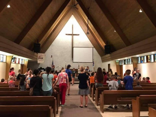 Large group of people in the sanctuary with Day Camp Leaders in front