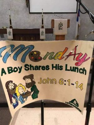 "Poster on a stand with ""Monday"" at the top and ""A Boy Shares His Lunch"" -the lesson for Monday"