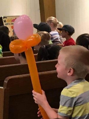 Boy seated in the sanctuary holding balloons twisted together.