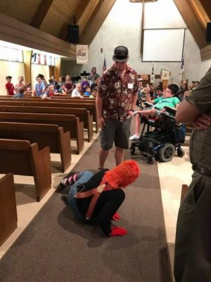 A man standing with a lady in costume is on the floor in the aisle in the sanctuary