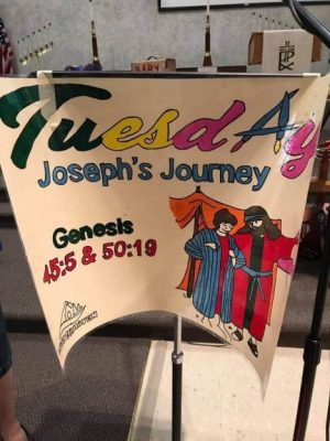 "Poster on a stand with the words ""Tuesday, Joseph's Journey."""