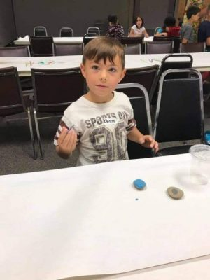 A boy at a table covered with white paper and two rocks that have been painted
