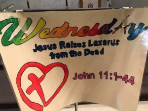 "Banner on a stand with ""Wednesday"" and ""Jesus raises Lazarus from the dead"""