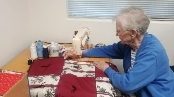 Photo of a lady using a sewing machine to sew a quilt.