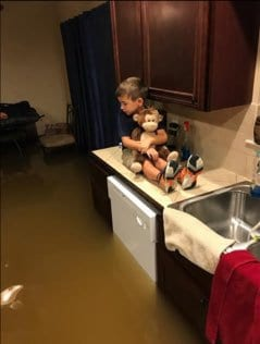 A boy on a kitchen counter holding a stuffed toy with water halfway up the dishwasher