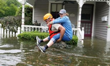 Photo of a man carrying a woman on his back through hip deep water in front of a house with water up to the door.