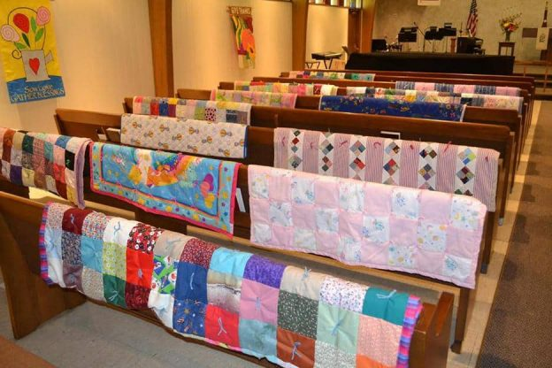 Mt Olive sanctuary with pews adorned with multi-colored quilts draped over the back of every pew