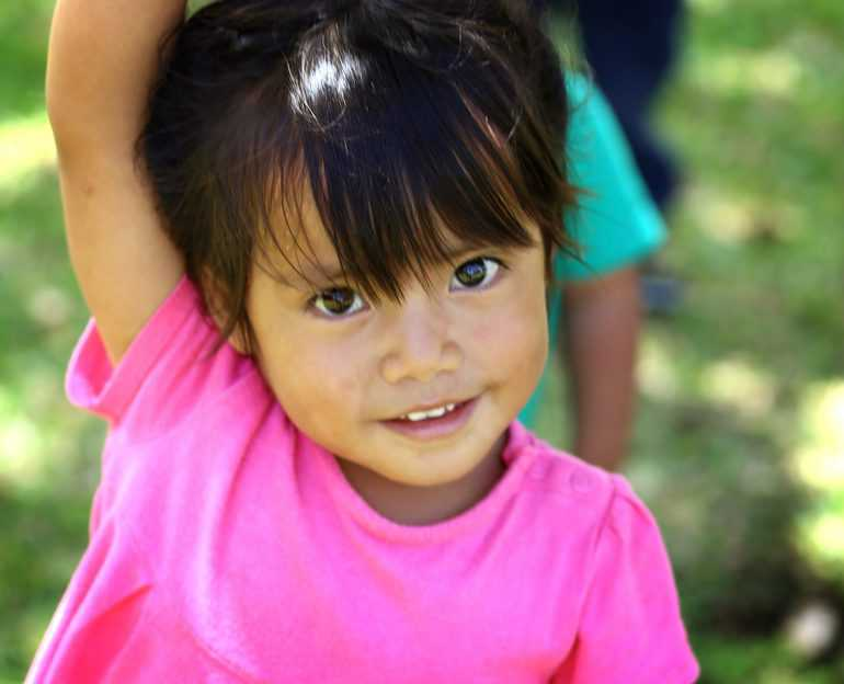 Young girl with pink tee shirt and dark hair smiling close-up