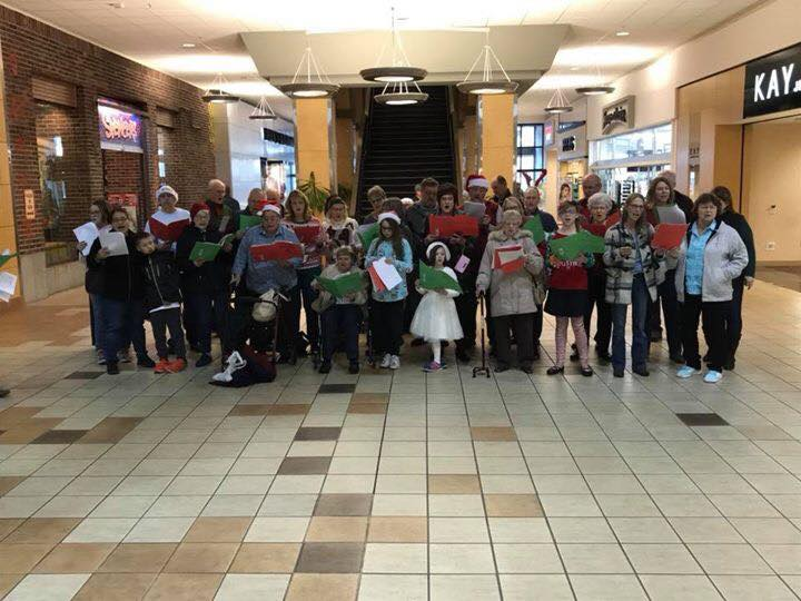 Large group of people standing in front of the stairs in the Valley Mall singing carols