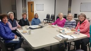 Photo of several ladies seated at a big table with Bibles open.