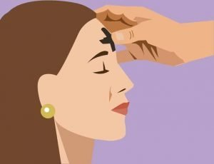 Woman with her eyes closed while a hand makes a black cross on her forehead.