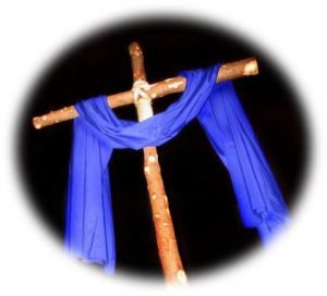 Photo of a cross made of small poles tied together and draped with a blue cloth against an all black background.