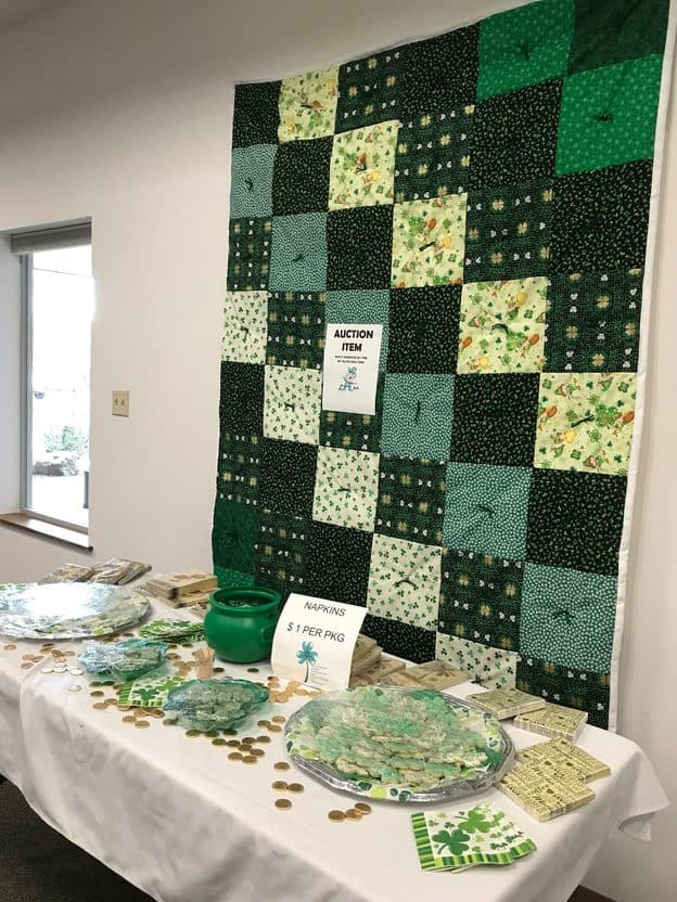 A green quilt hangs on the wall behind a table with homemade desserts