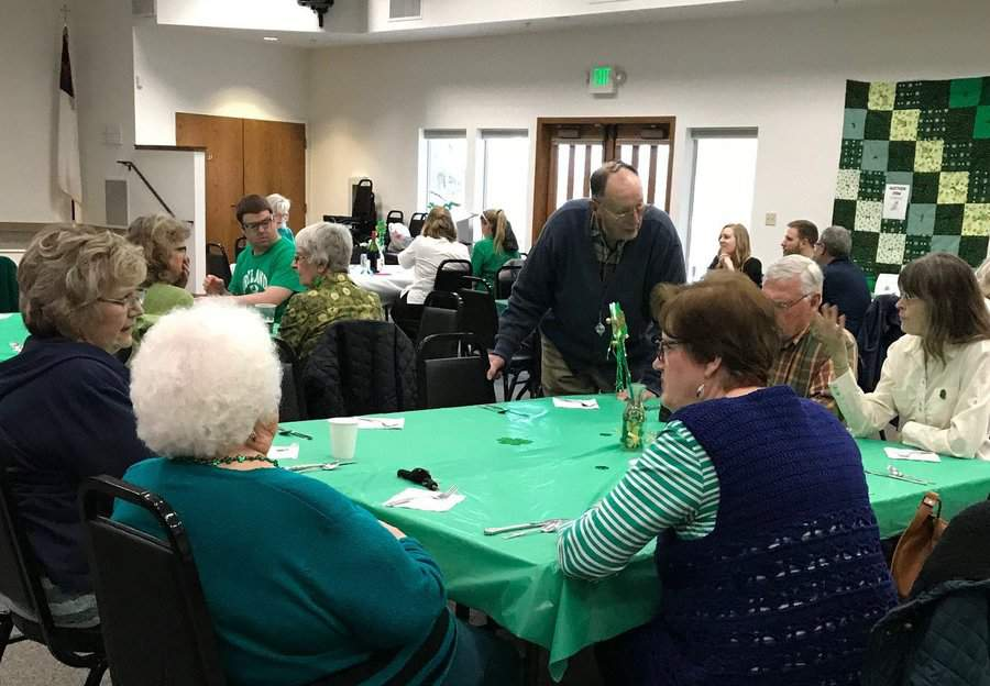 People talking around a table with a green table cloth in the Fellowship Hall