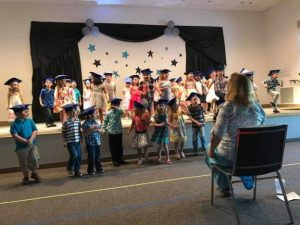 Photo of the stage in the Fellowship Hall with 30-40 children wearing graduation mortar boards with tassels on their heads.
