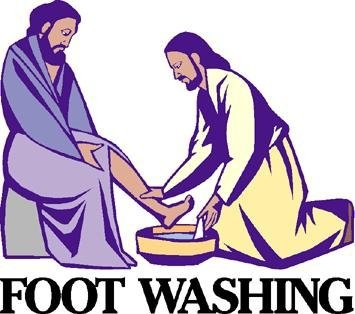 A man kneeling with a basin of water washing the other man's feet