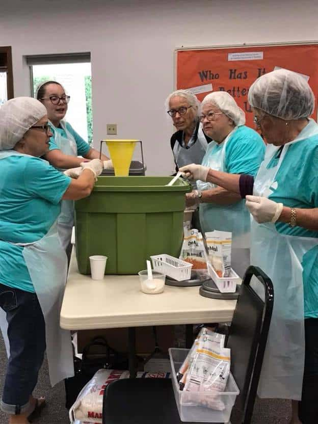 Ladies standing around a table wearing aprons with hair covered combining ingredients for meals.