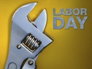 "Close-up photo of an adjustable wrench with the words ""Labor Day."""