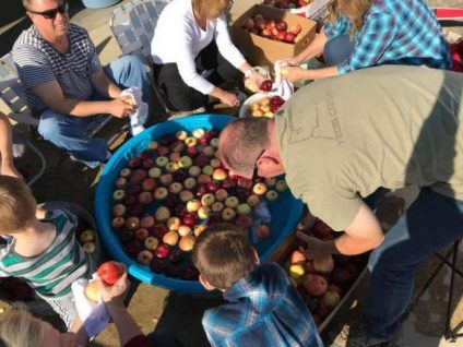 View from above of people around a plastic wading pool full of water and apples