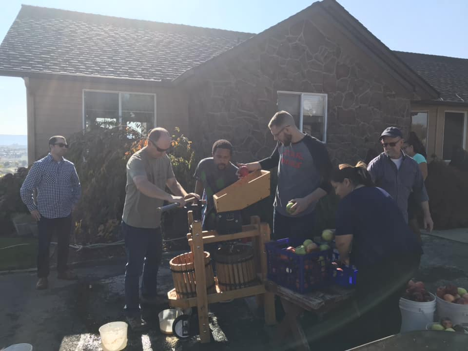 Photo of a group of people and children around the cider press making cider from apples