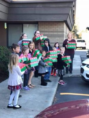 Photo of Sunday School children with their arms full of shoe boxes they are loading into a car