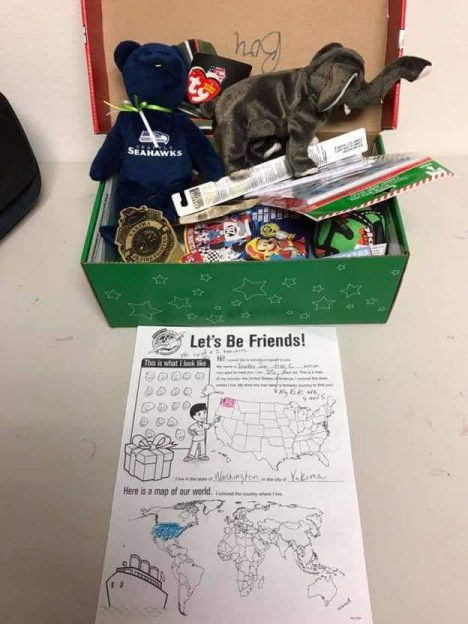 Photo of a shoe box full of a number of items and a paper laid on the table in front of the box